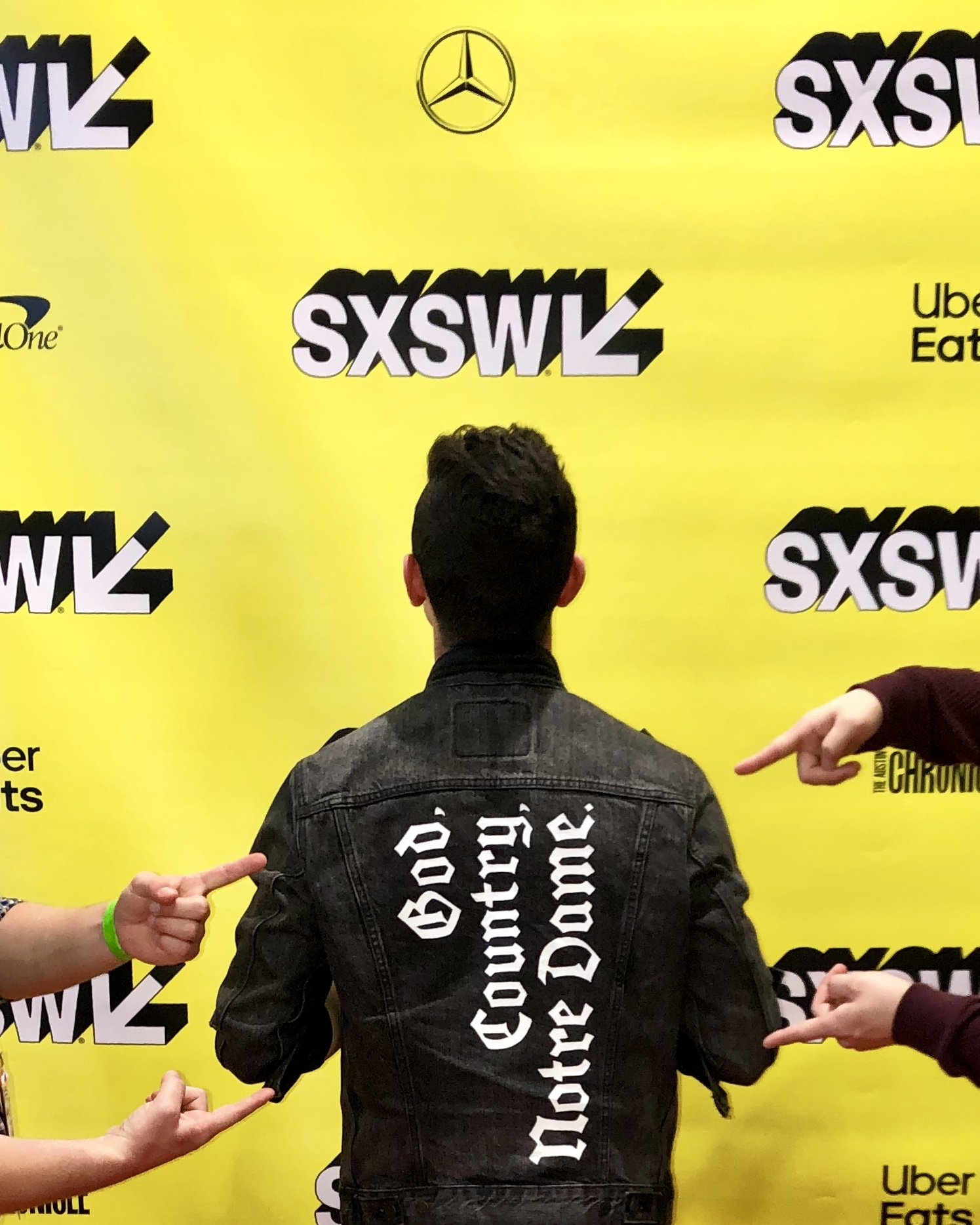 fingers point to the back of a jacket on a man reading: God. Country. Notre Dame. He stands in front of a SXSW backdrop