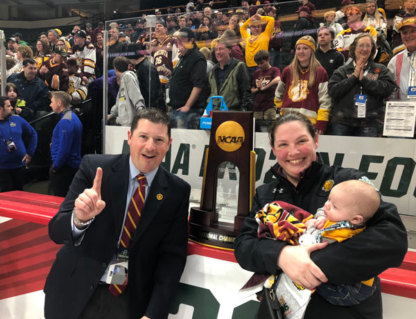 man and a woman holding a baby at a hockey game with an NCAA trophy