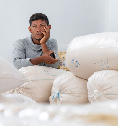 a man leans against large white bags of processed farinha