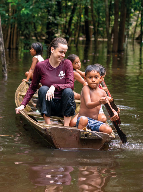 children guide a canoe on the river in the amazon with a young woman passenger