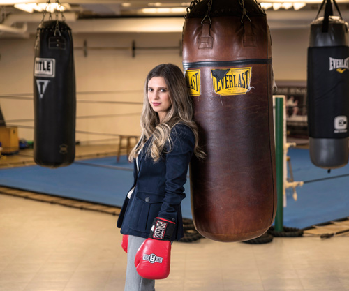 a woman in a business suit wears red boxing gloves and leans against a punching bag