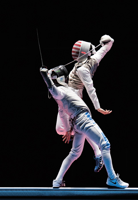 a fencer jumps in the air scoring on his opponent