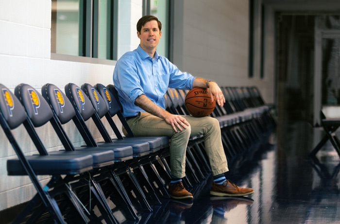 Peter Zanca sits on a row of chairs holding a basketball in the Indiana Pacers gym