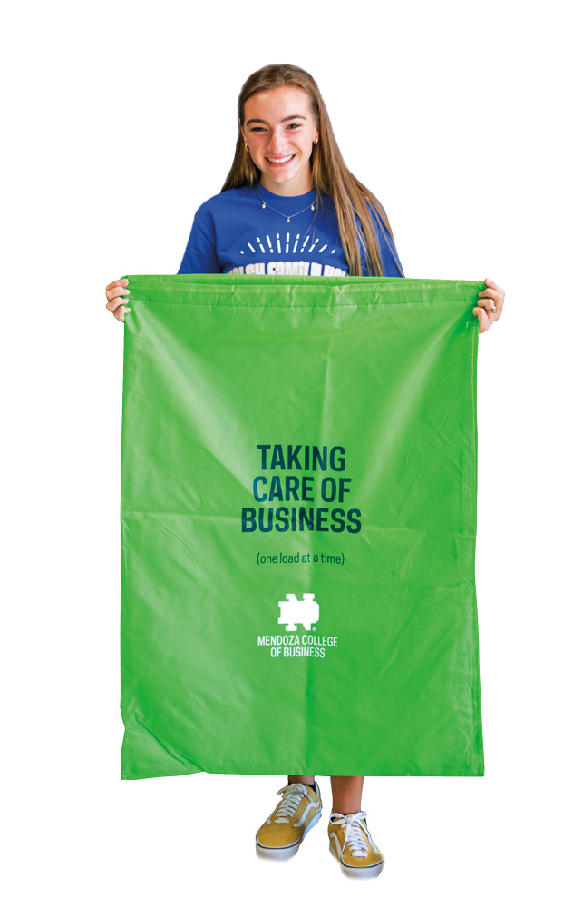 a student holds up a large green canvas laundry bag that says taking care of business one load at a time
