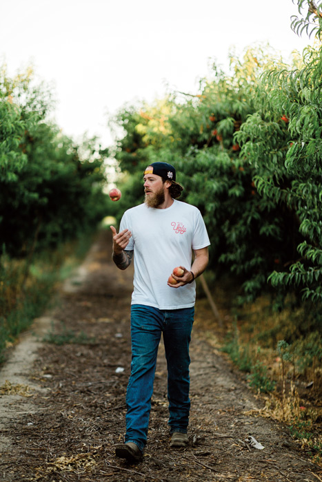 a man walks through a fruit grove tossing peaches in the air