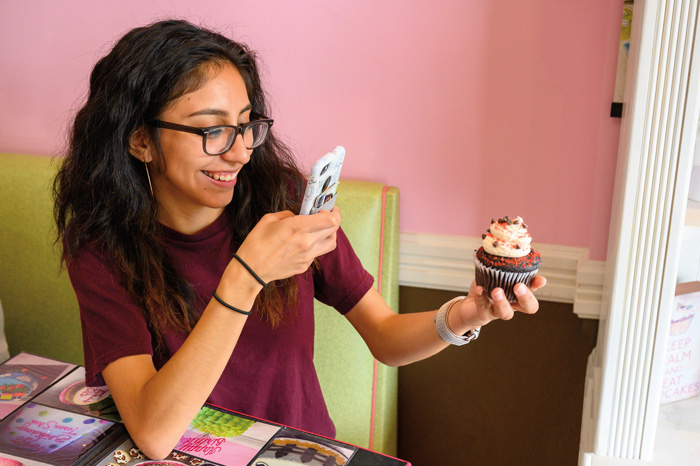 a student takes a photo of a fancy cupcake with her cell phone