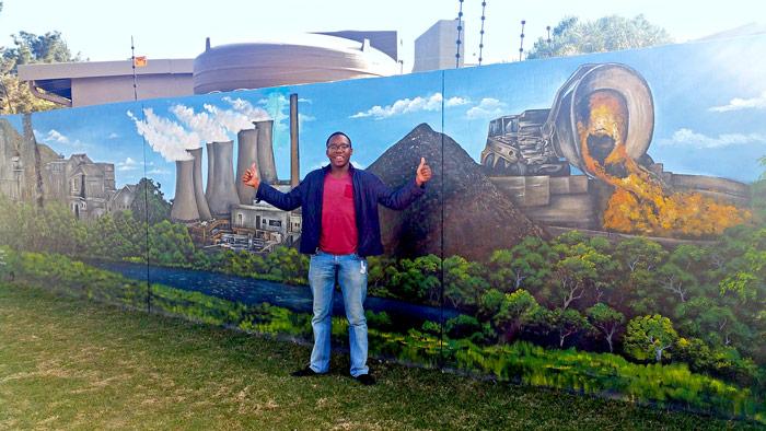 Takunda Ushe in front of a mural in Africa
