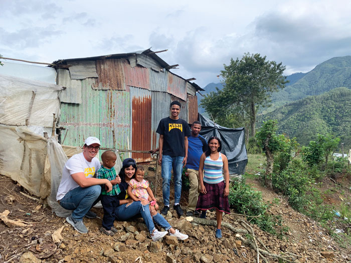 members of the puente group in front of a rusted metal house