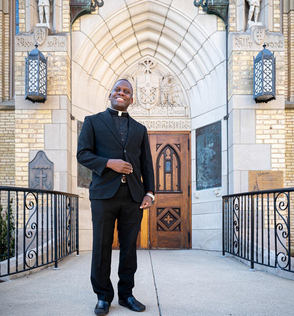 Fr. Arthur Ssembajja standing in front of chapple doors