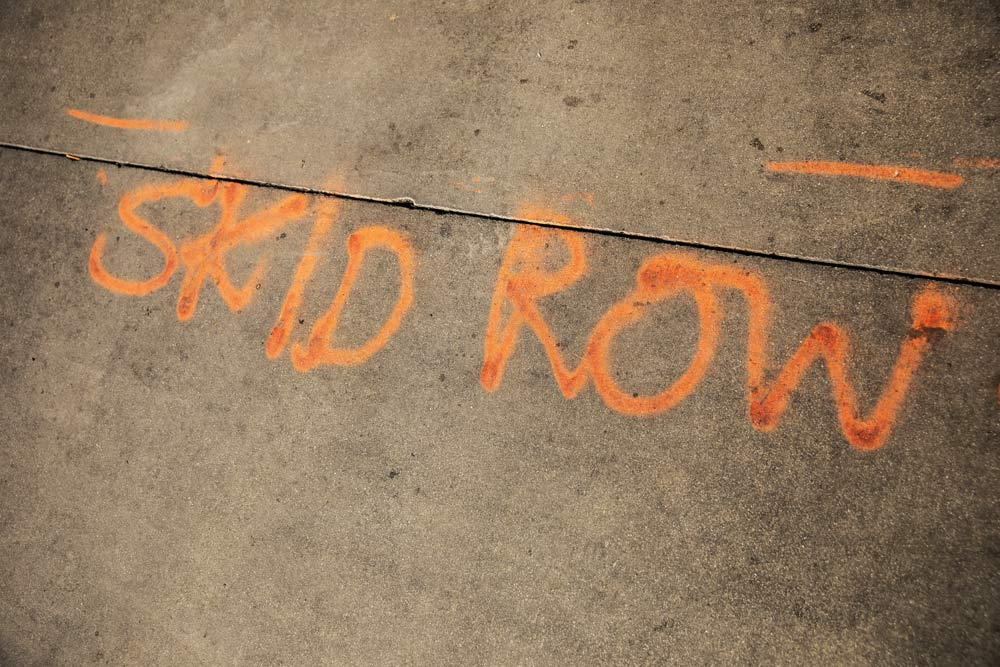 the words skid row spray painted on cement