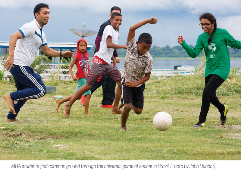 MBA students and kids in Brazil play soccer